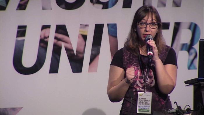 Foto da Talita Pagani, em pé, segurando um microfone. Ela tem cabelos lisos e longos e está usando óculos.
