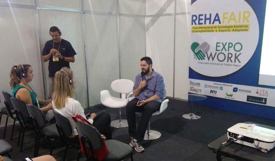 Foto do William sentado com um microfone na mão na frente de duas mulheres sentadas. Ao fundo, há um banner com o texto REHAFAIR.