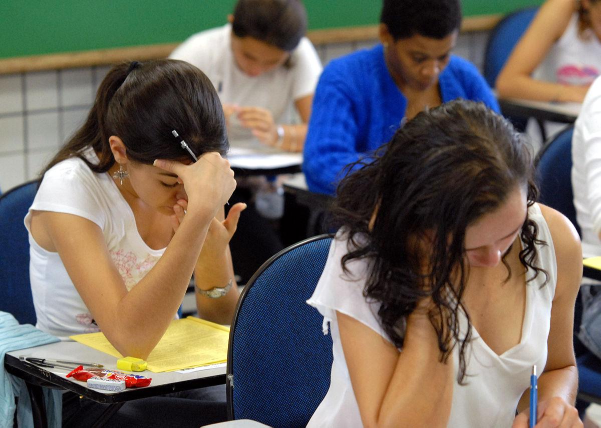 Foto de um grupo de estudantes sentados em carteiras, fazendo prova do Enem.