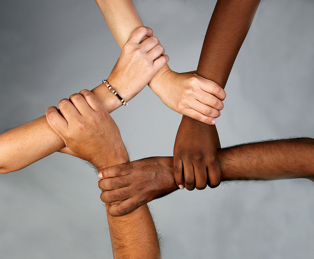 Foto de cinco mãos, de tons de pele diferentes, entrelaçadas formando um pentágono.