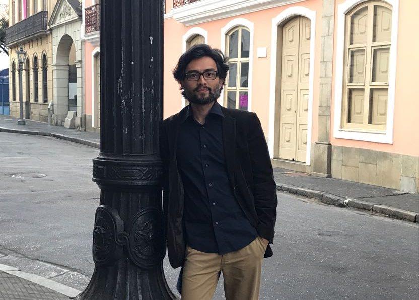 Foto do Alexandre Ohkawa, em pé, encostado em um poste. Ele é moreno, tem cabelos curtos, usa óculos.