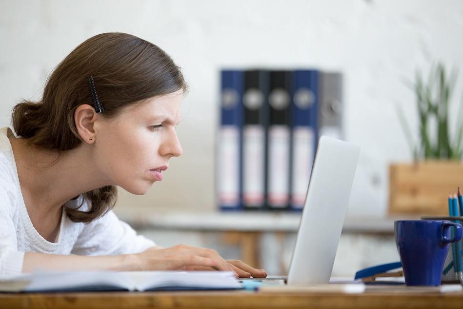 Jovem mulher branca com cabelos castanhos. Ela está com rosto próximo à tela do laptop, com dificuldades para enxergar.