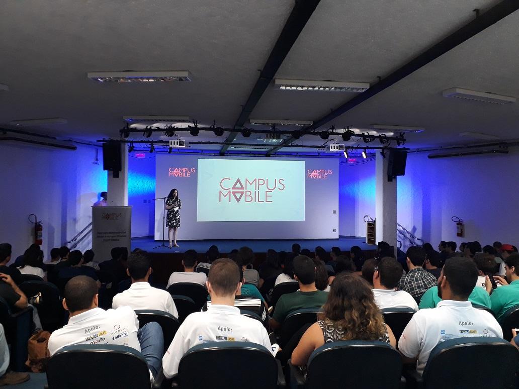 Foto de uma mulher em pé em um palco na frente de uma platéia lotada. Ao fundo, atrás da mulher, há um telão com o logo da Campus Mobile.
