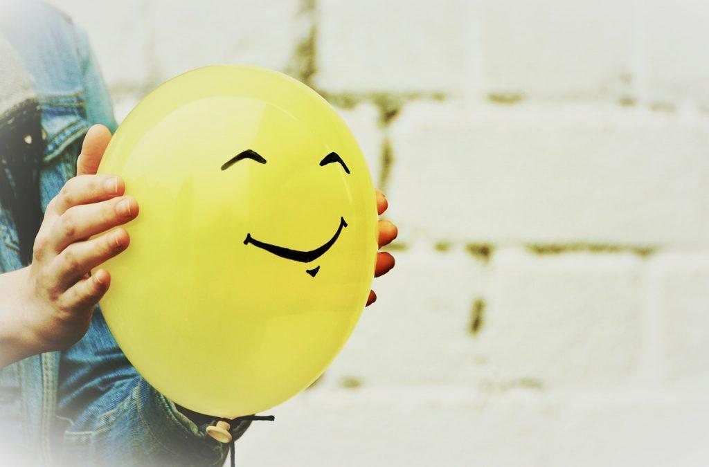 Foto de uma pessoa segurando uma bexiga amarela. Há um rosto com um sorriso desenhado nela.