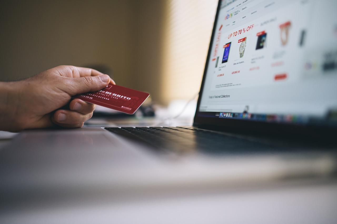 Foto de uma mão segurando um cartão de crédito em frente a um laptop. Na tela, há fotos de relógio e outros produtos que estão desfocados.