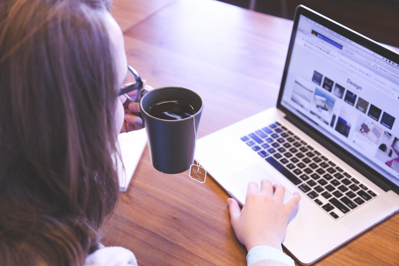 Foto de uma pessoa de óculos segurando uma caneca olhando a tela de um laptop. Uma das mãos está no teclado do laptop.