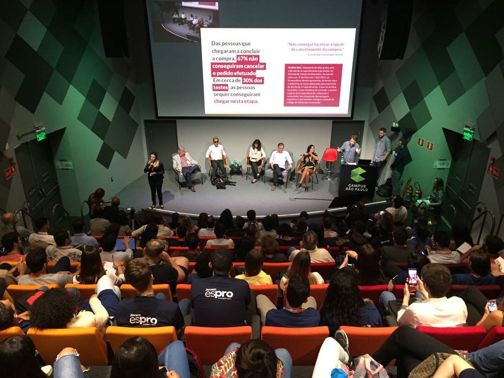 Foto de um homem falando ao microfone em frente ao auditório lotado do Google Campus São Paulo. Ao fundo, há um telão com texto da pesquisa.