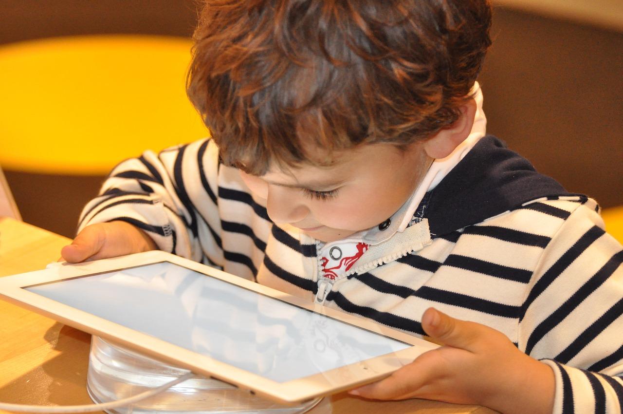 Foto de uma criança segurando um tablet com as duas mãos. Ela sorri e está com o rosto muito próximo à tela.