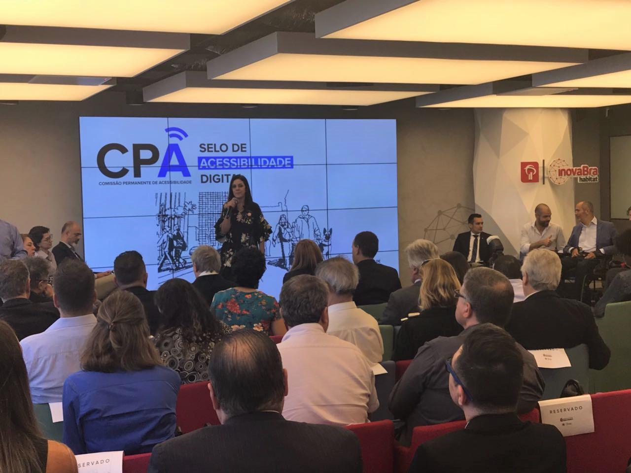 """Foto da Simone Freire em pé, segurando um microfone na frente de um público sentado em uma sala fechada. Ao fundo, há um telão com o texto """"CPA - Comissão Permanente de Acessibilidade. Selo de Acessibilidade Digital""""."""