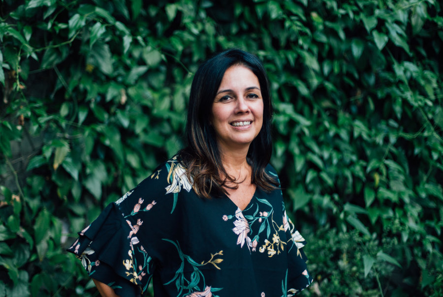 Foto da Simone Freire sorrindo. Ela é morena, tem cabelos lisos, castanhos e está usando um vestido florido.