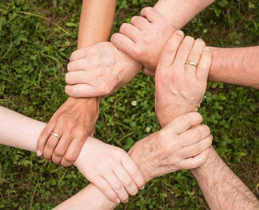 Foto de seis mãos diferentes entrelaçadas com grama e flores ao fundo. Cada uma delas está segurando a outra pelo pulso, formando um hexágono.