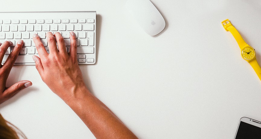 Foto de duas mãos em um teclado branco. Há um mouse branco e um relógio amarelo ao lado.