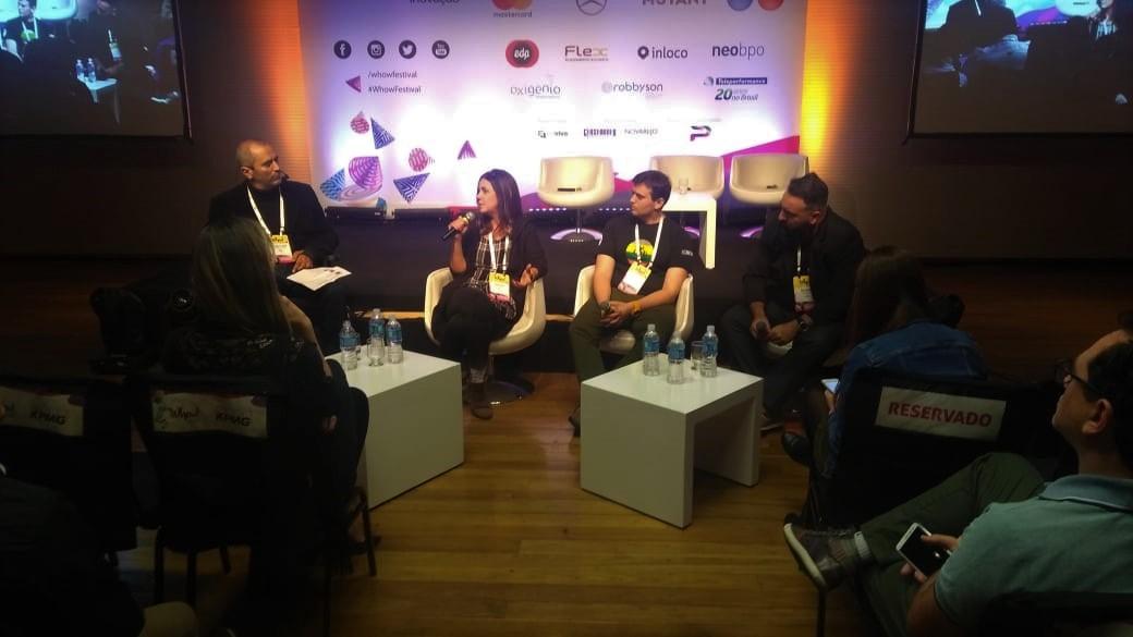 Foto da Simone Freire sentada, falando ao microfone, na frente de uma plateia. Cid Torquato, Julio Oliveto e Caio Esteves estão sentados ao lado dela.
