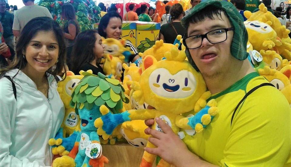 Foto da Débora ao lado do David sorrindo. Eles estão em pé, segurando bonecos com logos das Paralimpíadas 2016.