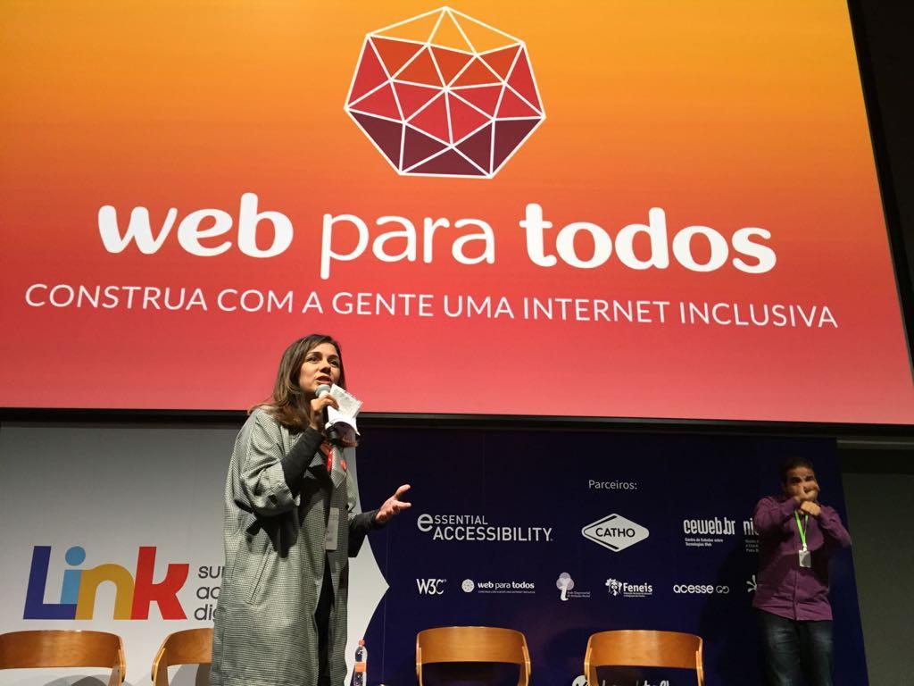 Foto da Simone Freire no palco do Google Campus. Ela está pé, falando ao microfone, olhando para o público.