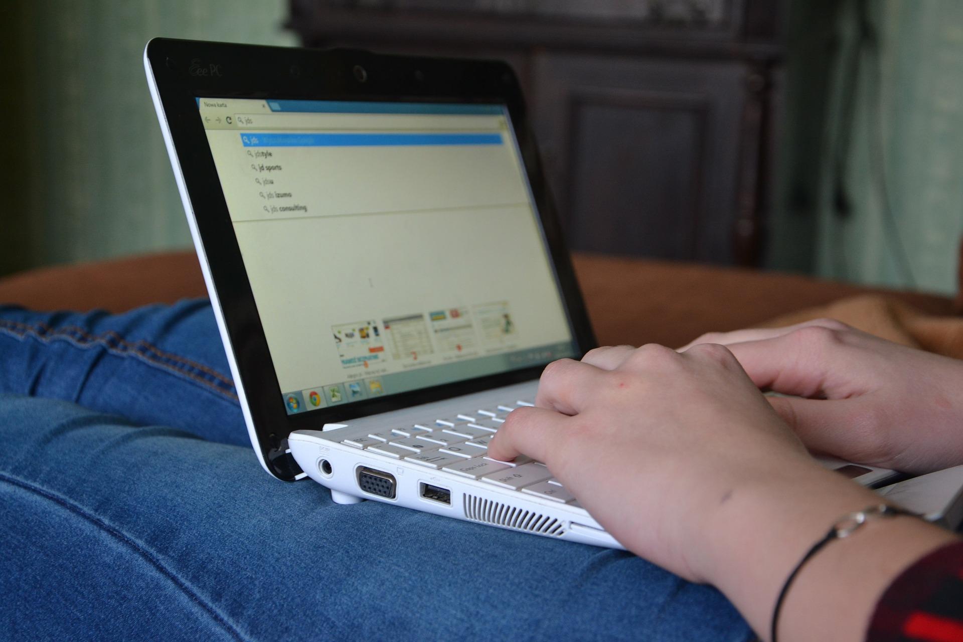 Pessoa sentada com um laptop nas pernas e com as mãos no teclado do equipamento. A tela mostra diversas palavras na ferramenta de busca do navegador.