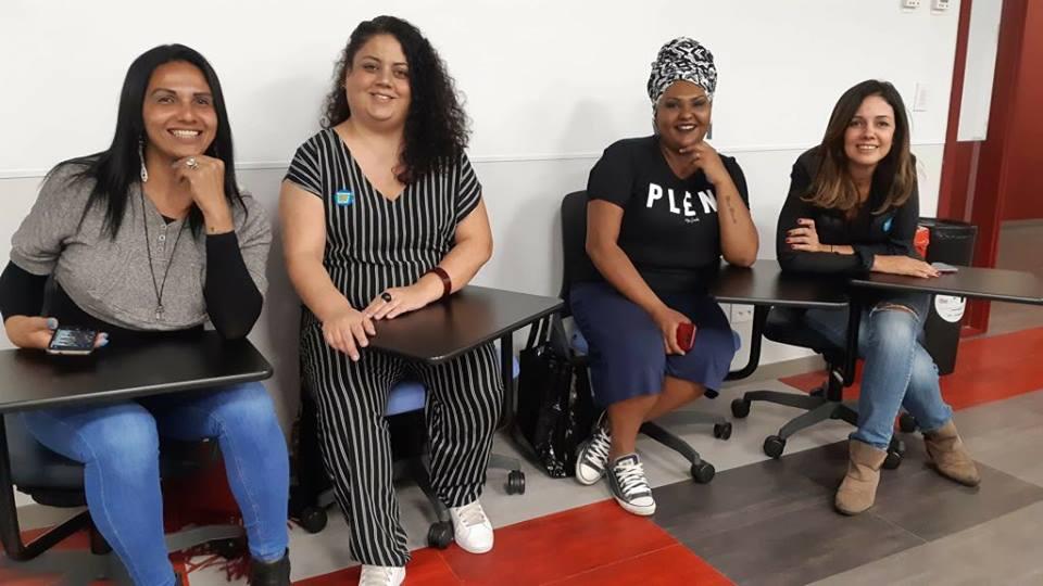 Rubi de la Fuente, Flavia Durante, Michelle Fernandes e Simone Freire sorrindo. Elas estão sentadas em cadeiras do tipo estudante em uma sala.