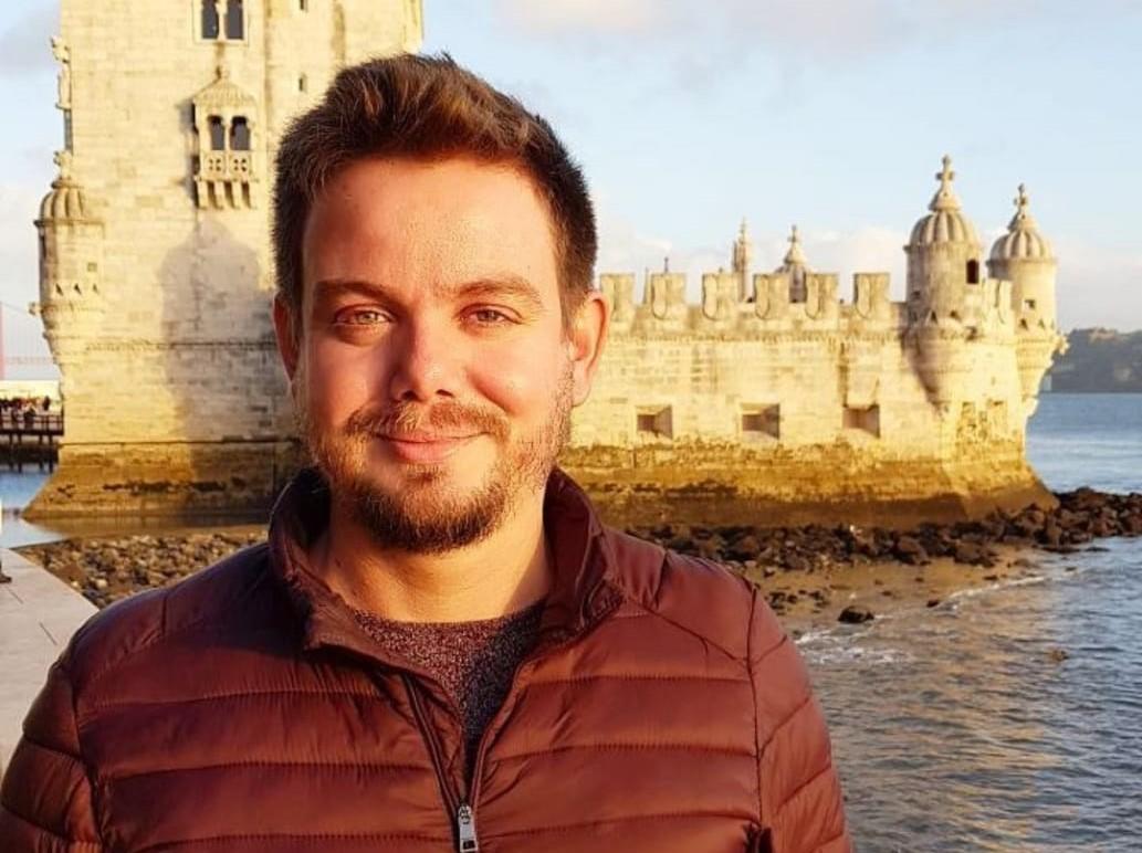 Foto do Valter Lenine Fernandes sorrindo. Ele está em um ambiente externo, próximo ao mar. Ao fundo, há um castelo. Ele é loiro, tem olhos claros e cabelos curtos.