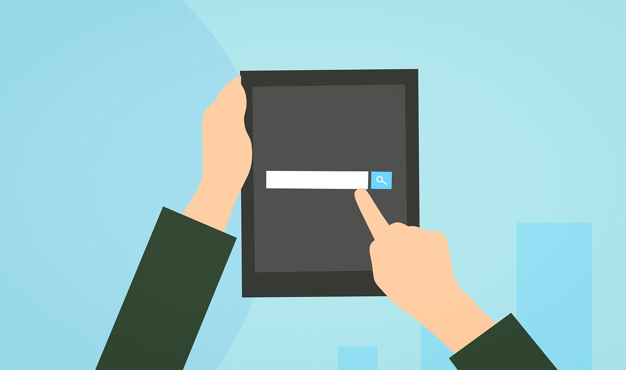 Ilustração de uma pessoa segurando um tablet com uma das mãos e tocando a tela com a outra. Na tela, um campo de busca.