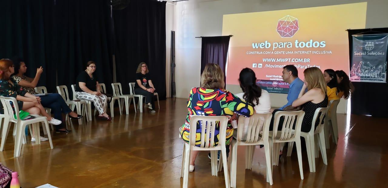 Pessoas sentadas em cadeiras organizadas em roda. Ao fundo, há uma imagem grande projetada na parede com o logo do Movimento Web para Todos e dois banners do Social Soluções em cada lado.