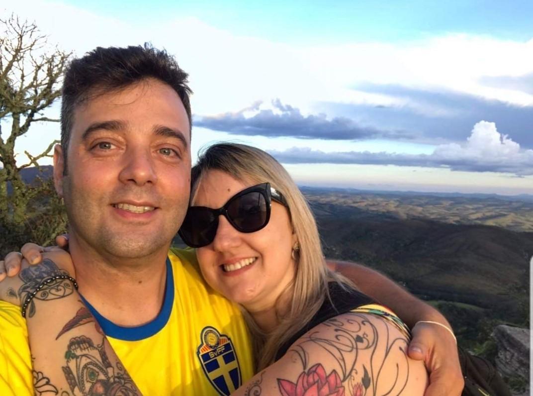 Matheus e Karina estão abraçados em uma área externa em um dia ensolarado. Ambos sorriem. Ao fundo, há uma área verde.