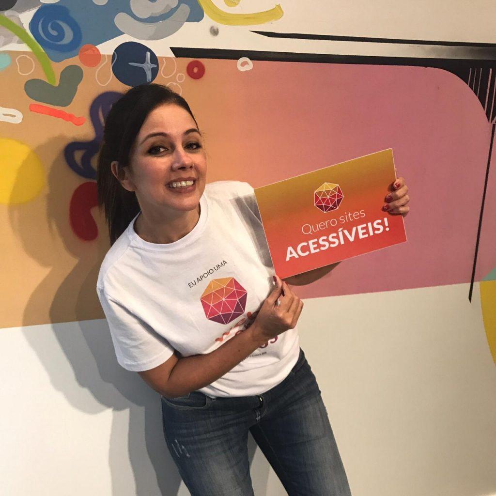 """Simone Freire está em pé, sorrindo, segurando uma placa com a frase: """"Quero sites acessíveis""""."""