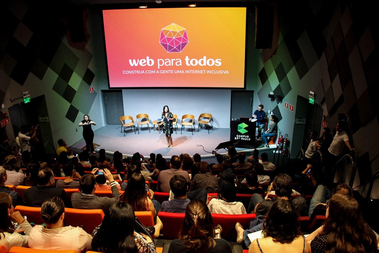 Foto de um auditório lotado, visto de cima. No palco, há uma mulher morena que fala ao público, com uma tela ao fundo que projeta o logo do Movimento Web para Todos.