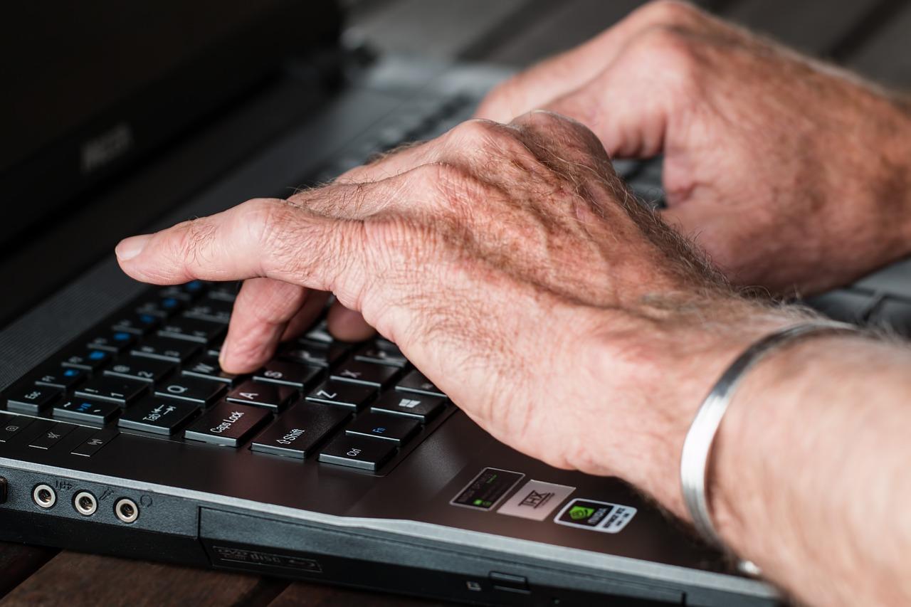 Foto das mãos brancas de uma pessoa idosa no teclado de um laptop. Alguns dedos encostados em teclas específicas do teclado.