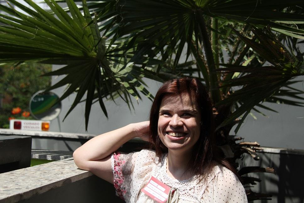 Foto de uma mulher branca com cabelos longos sorrindo. Ela está com o braço direito apoiado em um muro baixo. A mão direita apoia a cabeça dela.