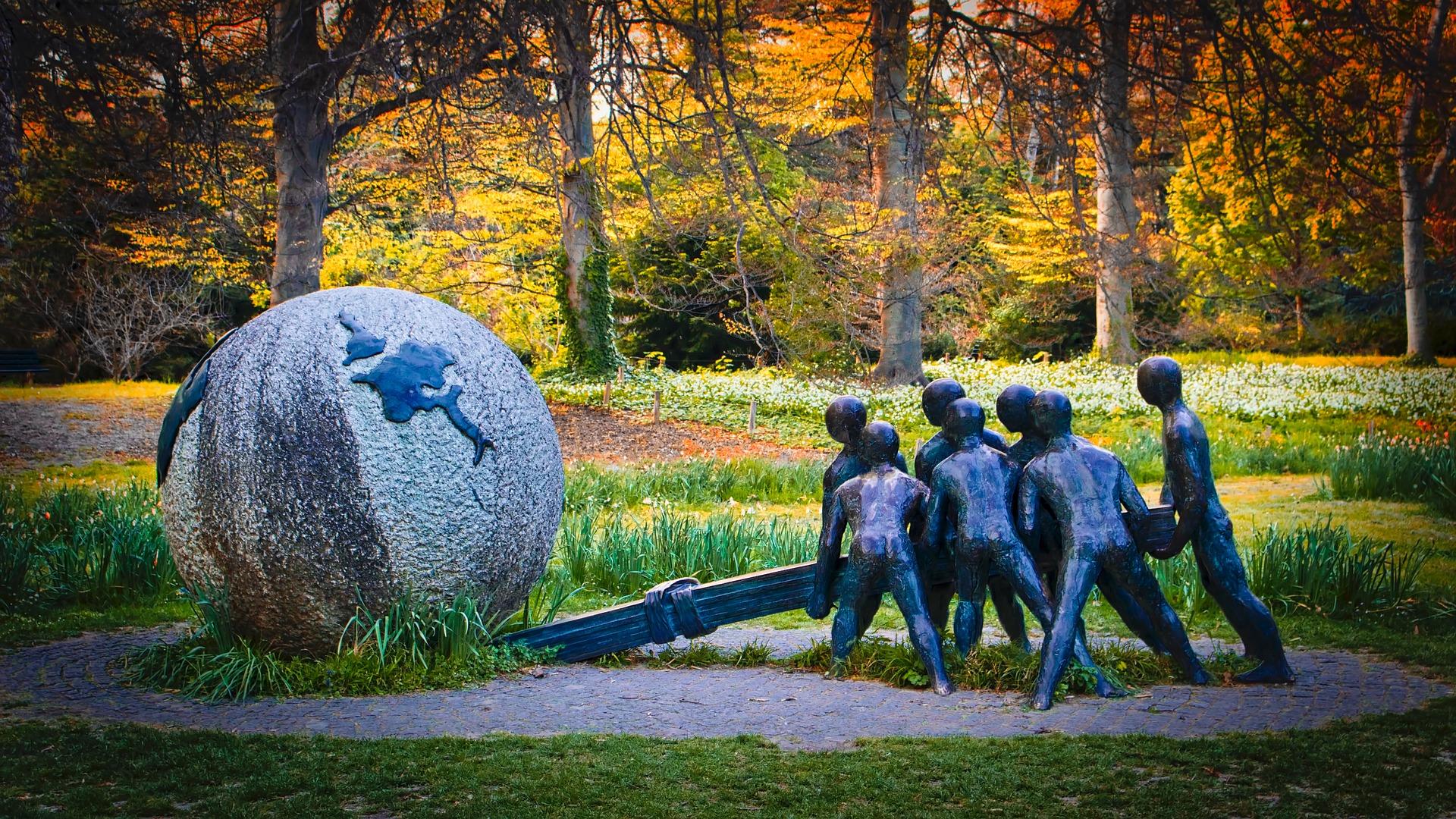 Foto de um ambiente arborizado e gramado, onde há uma escultura. A escultura representa um globo terrestre e sete pessoas somando forças para movê-lo utilizando uma alavanca.
