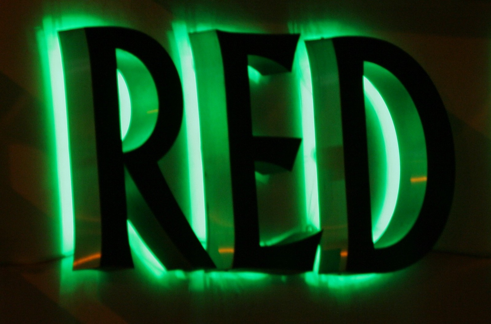 Foto da palavra red em destaque e luz neon verde no contorno de cada letra.