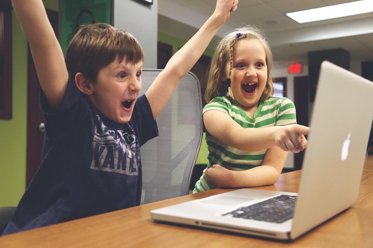 Foto de uma menina e um menino sentados na frente de um laptop. Eles olham para a tela com expressões faciais que demonstram muita alegria.
