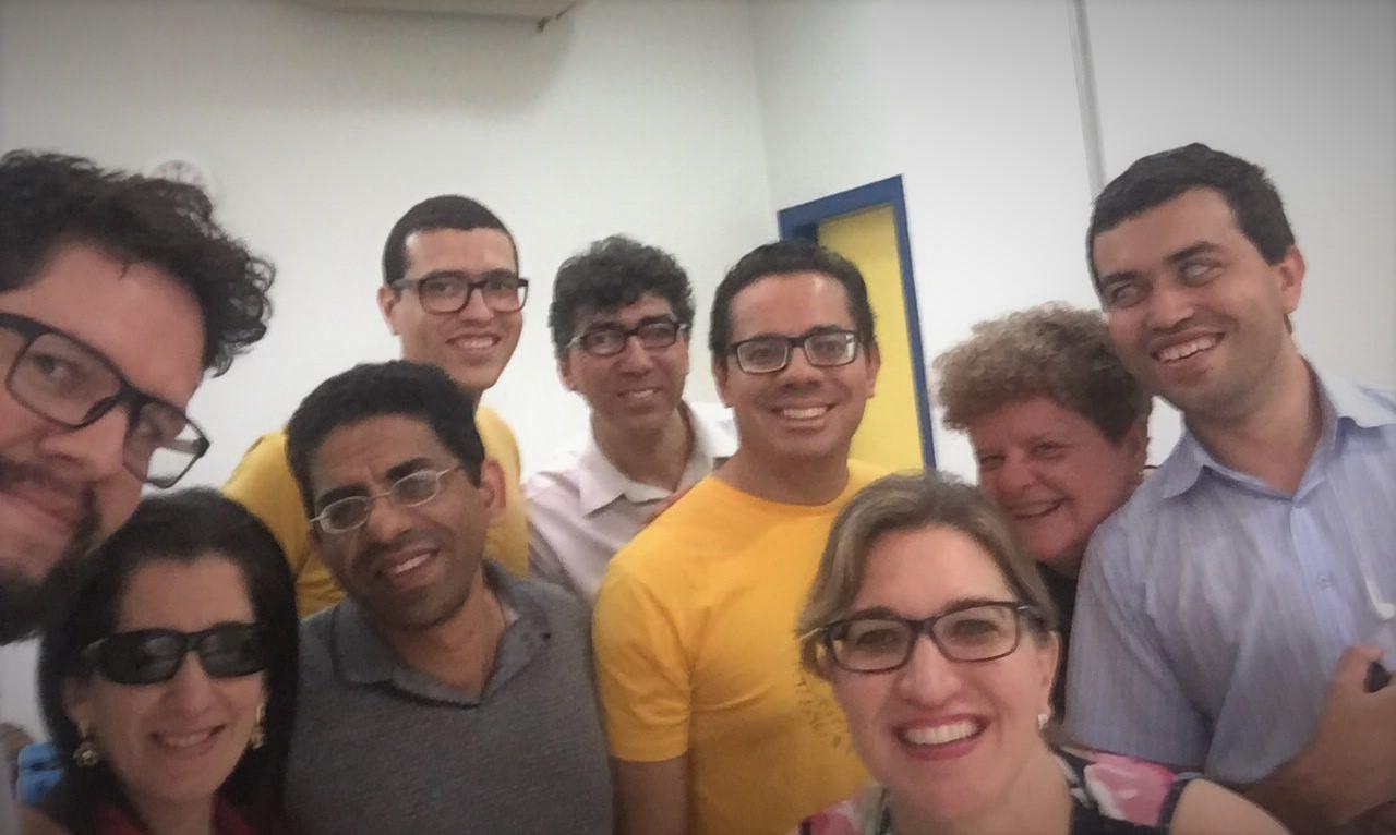 Foto do William e da Suzeli com homens e mulheres sorrindo em uma sala fechada.