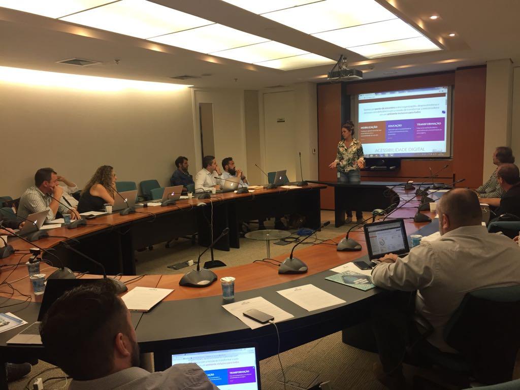 Foto de uma sala com pessoas sentadas observando Simone em pé. Ao fundo, há um telão com a página principal do Web para Todos.