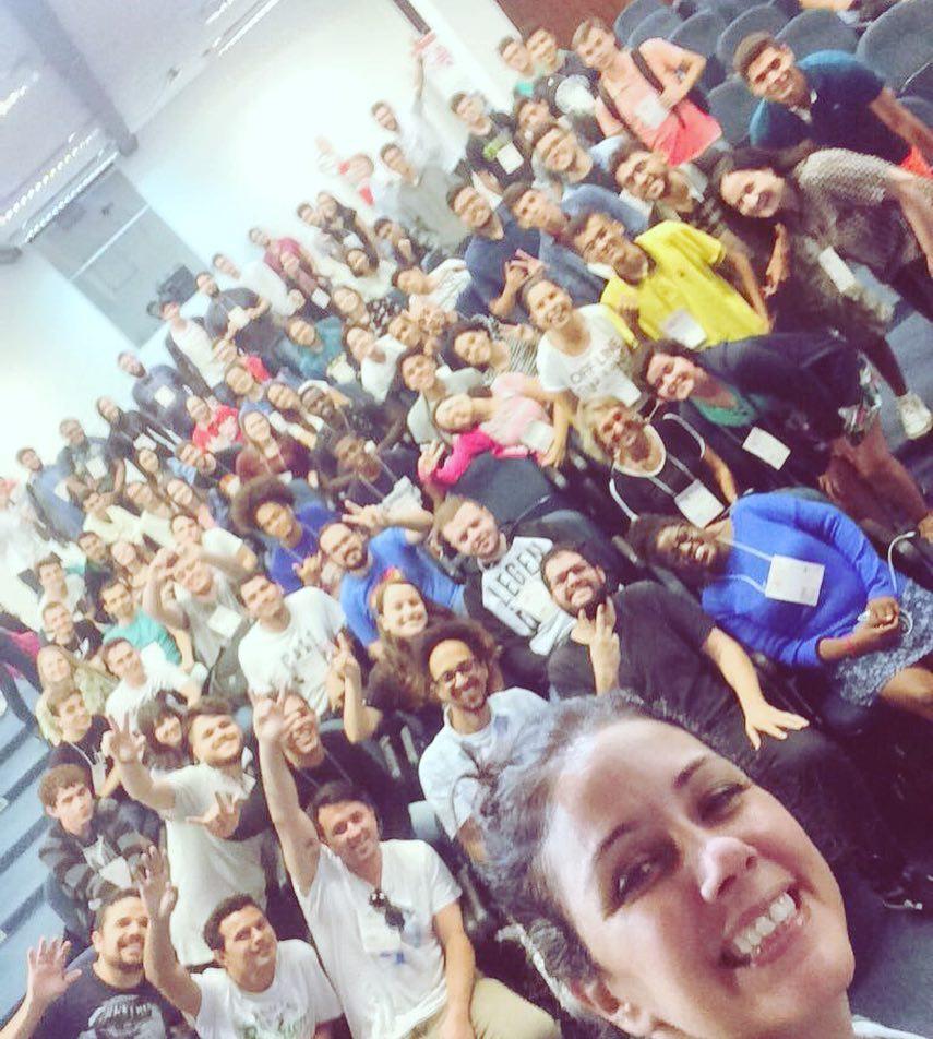 Foto estilo selfie da Simone com participantes do Campus Mobile ao fundo sorrindo. Alguns estão com braços levantados fazendo sinal de V e coração com as mãos.
