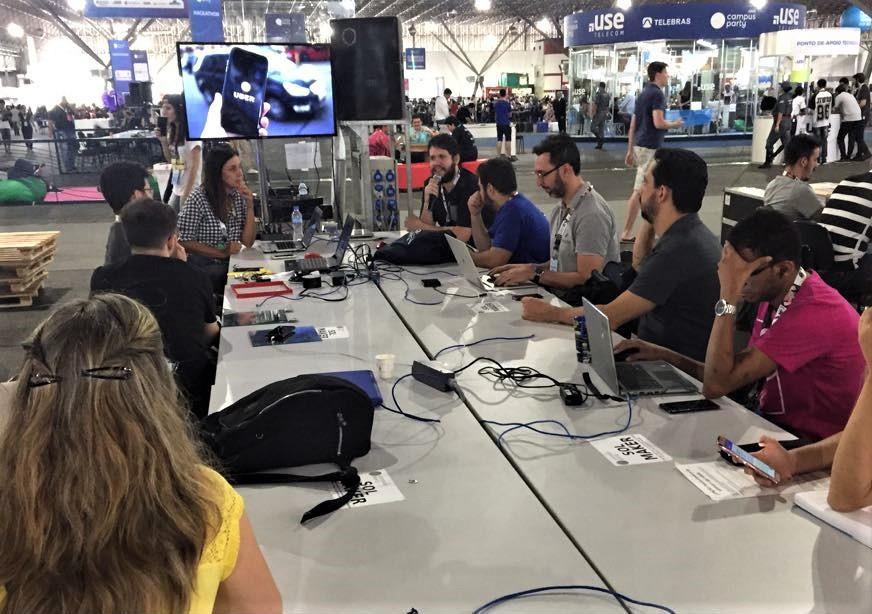 Foto de um espaço aberto com pessoas reunidas ao redor de uma mesa retangular com laptops. Na ponta da mesa, William seguram microfones e falam para os participantes.