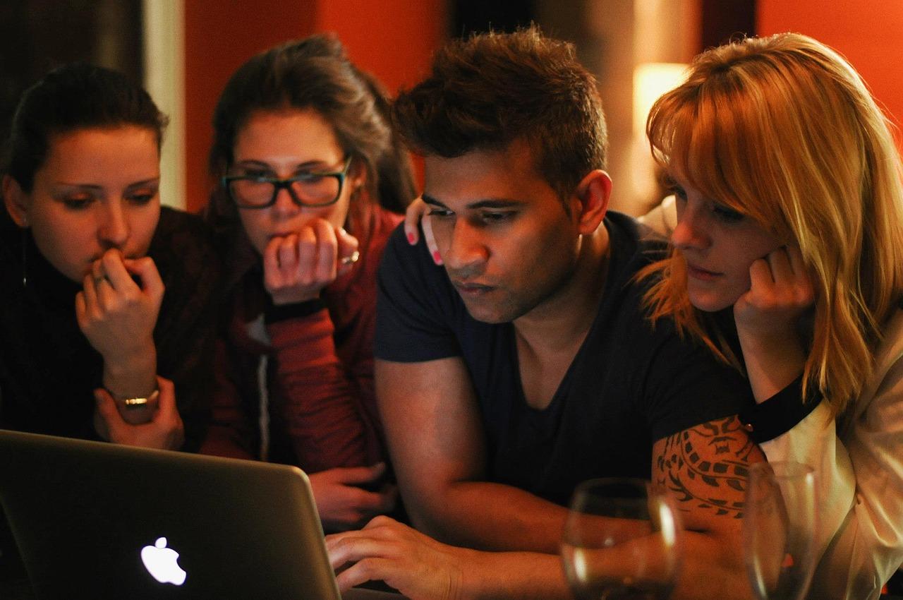Foto de quatro pessoas olhando a tela de um laptop. Há três mulheres e um homem com uma das mãos no teclado.