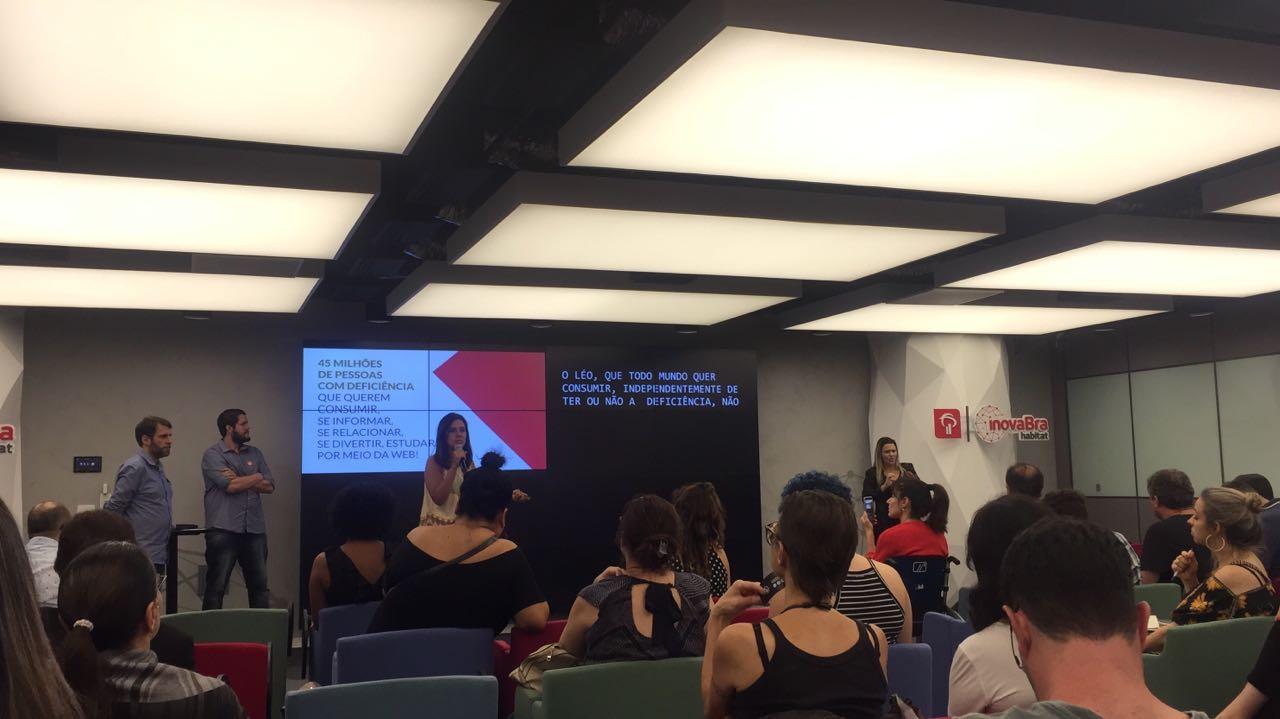 Foto de uma mulher segurando um microfone em frente a uma plateia sentada, em um ambiente fechado.