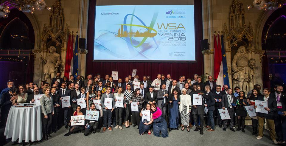 Foto de pessoas reunidas segurando diplomas. Ao fundo, há um telão com o texto: WSA 2018.