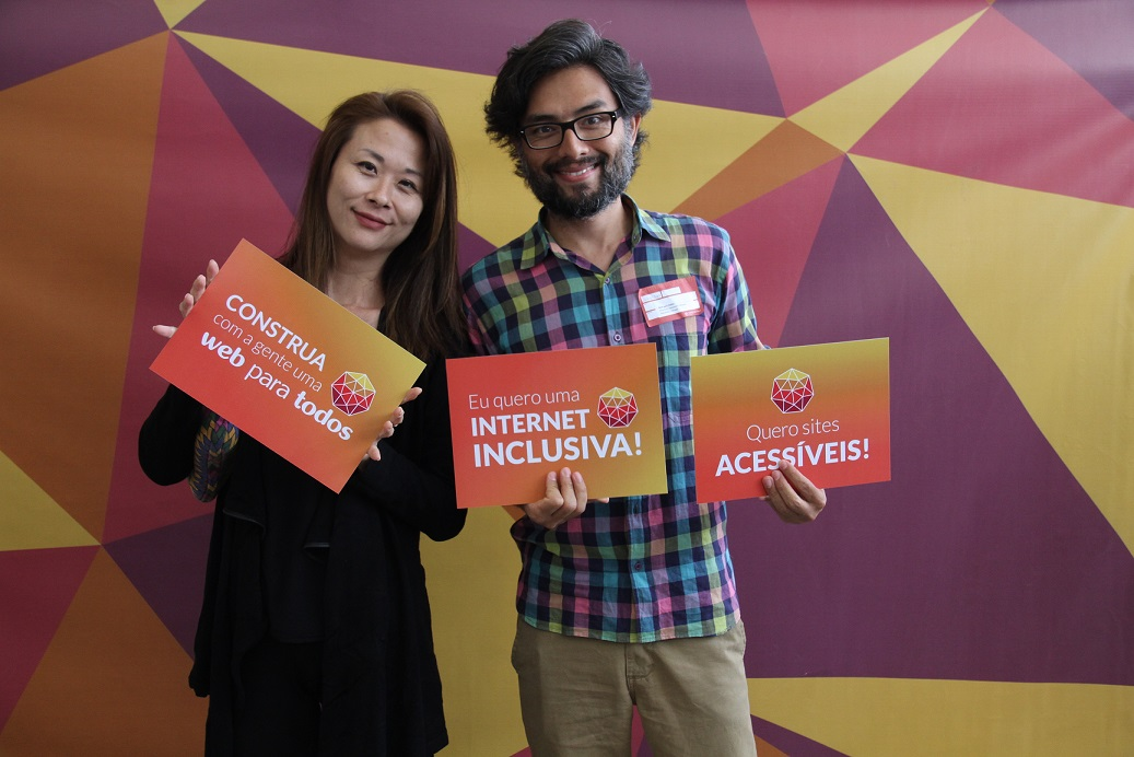 Romi e Alexandrei, em pé, sorrindo, segurando placas com o logo do Web para Todos.