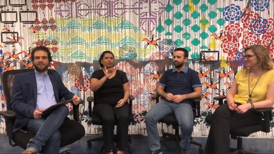 Dois homens e duas mulheres estão sentados, conversando. Ao fundo, há uma arte colorida.