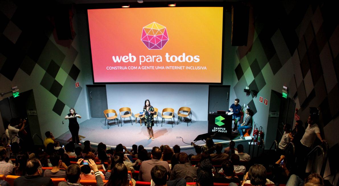 Simone Freire em pé em um palco na frente de pessoas que estão sentadas em um auditório. Ao fundo, há um telão com o logo do Web para Todos.