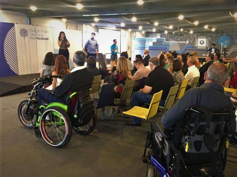 Simone Freire, em pé, falando ao microfone em uma sala grande, na frente de pessoas sentadas. Ao fundo, há um banner com o texto: Estação Hack.