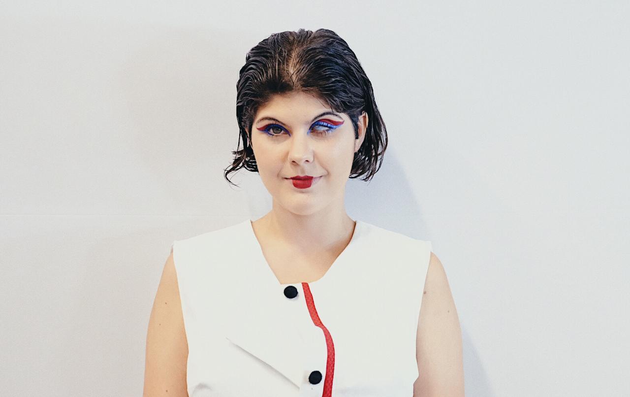 Isa usa um vestido branco sem mangas que tem uma listra vermelha vertical na parte central e dois botões pretos ao lado. Ela tem cabelos castanhos que estão na altura da boca. Tem o olho direito verde e o esquerdo azul.