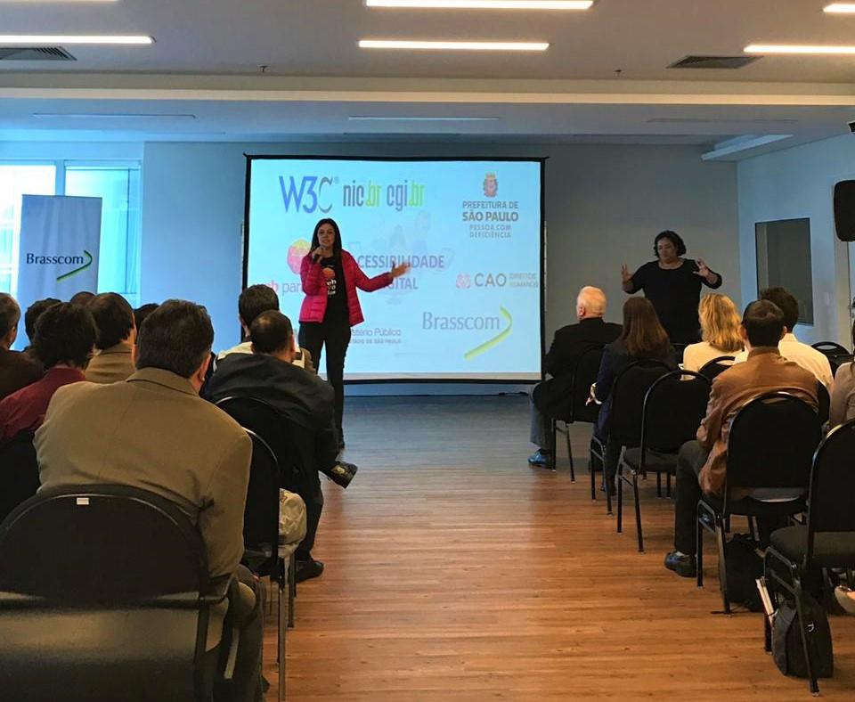 Simone Freire está em pé, falando ao microfone, na frente de pessoas que estão sentadas. Eles estão em uma sala.