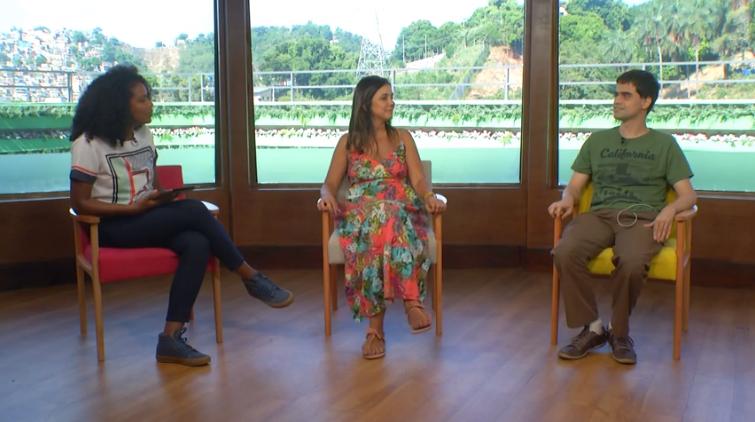 Três pessoas sentadas lado a lado em cadeiras separadas. Da esquerda para a direita, Karen de Souza, Simone Freire e Marcos Silva. Ambas olham para o lado direito, em direção ao Marcos.