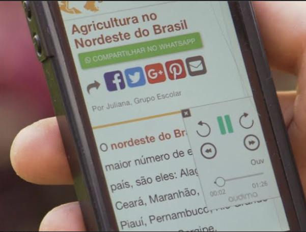 Mão de uma pessoa segurando um celular. A tela mostra uma notícia com a plataforma Audima.