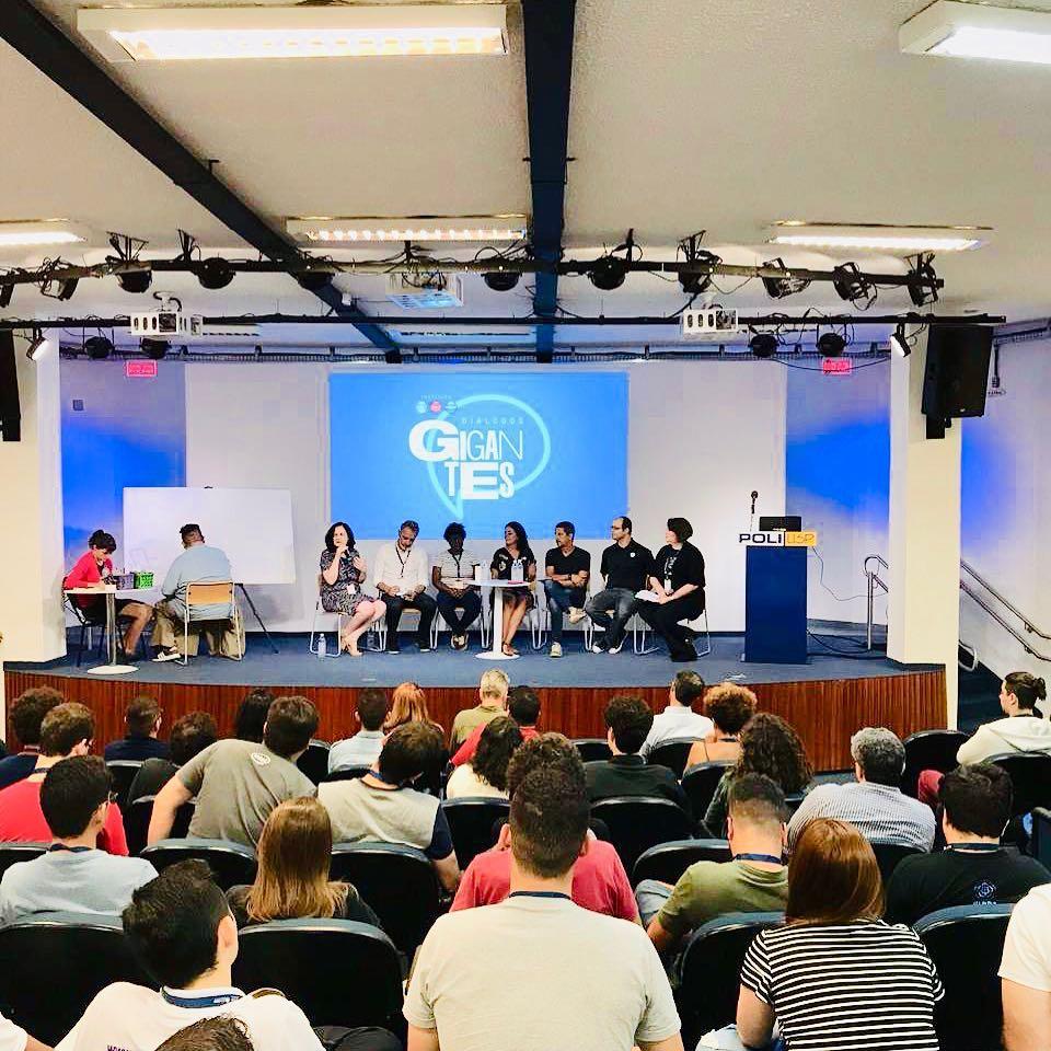 Auditório lotado da Escola Politécnica da USP. Simone Freire está no palco, sentada, ao lado de profissionais convidados. Ao fundo, há o logo Diálogos Gigantes.