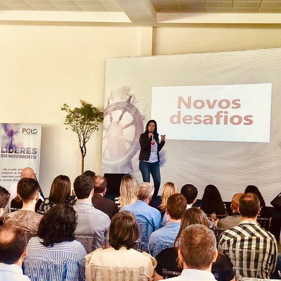 """Simone Freire, em pé, está em um palco falando ao microfone em um lugar fechado. A plateia está sentada olhando pra ela. Ao fundo, há um telão com o texto """"Novos Desafios""""."""
