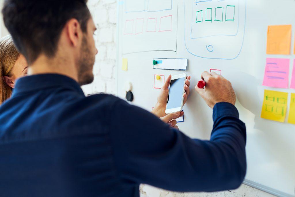 Homem está escrevendo em um quadro branco ao lado de uma pessoa que segura um celular na frente dele.